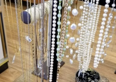 Yellow Gold, White Gold, and Pearl Necklaces on Display